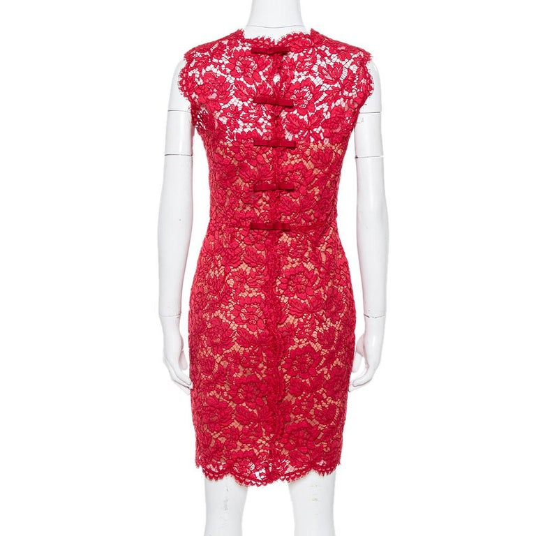 This stylish and chic dress by Valentino is perfect for special occasions and evenings. Crafted from intricate lace, it carries a striking hue of red and has a sleeveless silhouette. The sheath dress has a high neckline, scalloped edges along the