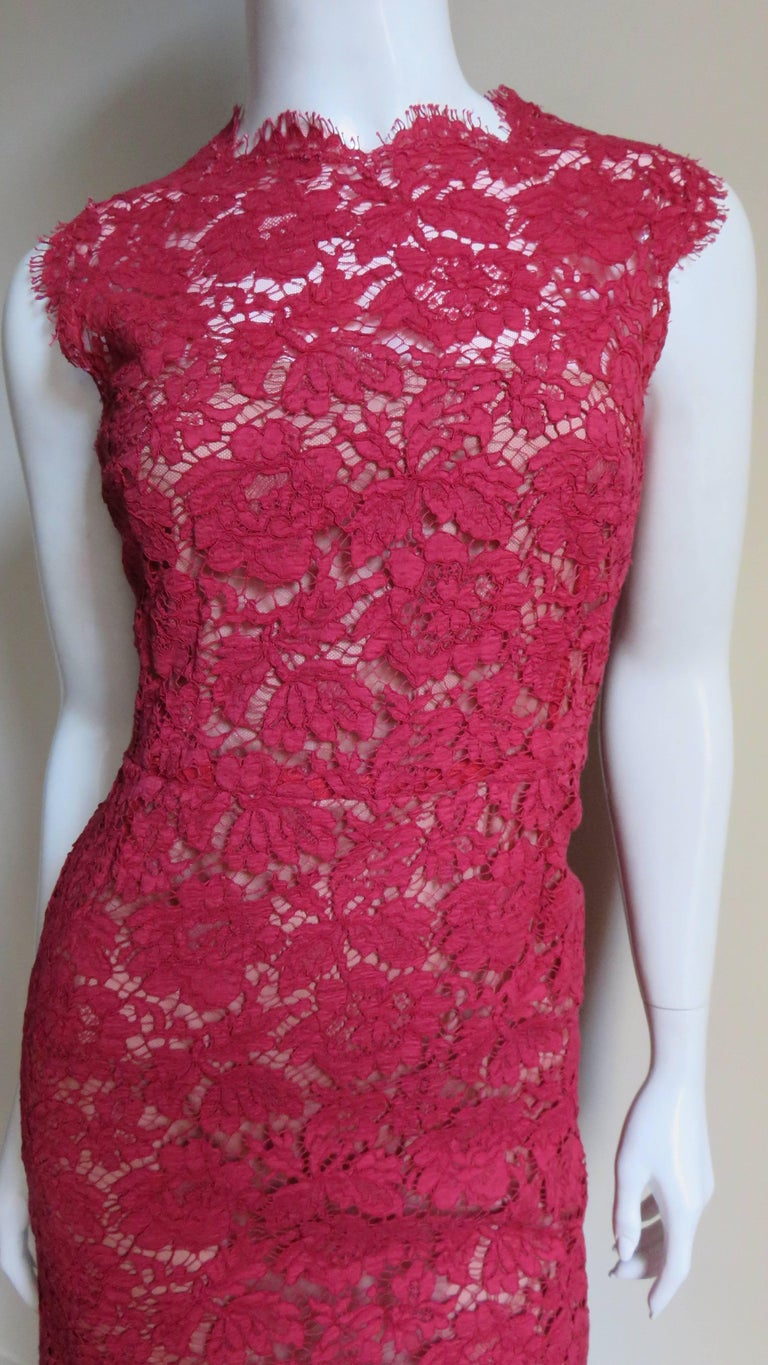 A beautiful red lace dress from Valentino.  It is semi fitted with the crew neck, arms, center back and hem of the straight skirt all finished in the scallop edge of the flower and leaves pattern lace. It has a nude colored lining, the upper back