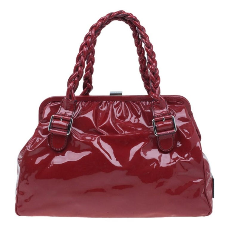 This Valentino bag from the Histoire collection is designed with a historic aesthetic reminding us of museums. Made from patent leather in a red shade, it features double top braided leather handles with gunmetal buckles, two front flap pockets, and
