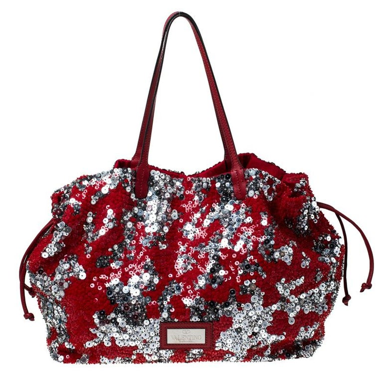 This elegant bag by Valentino will surely leave you spellbound. Made from fabric and leather and covered in sequins, the bag features drawstrings on the sides, two top handles, and a spacious satin interior. Glam up your wardrobe with this