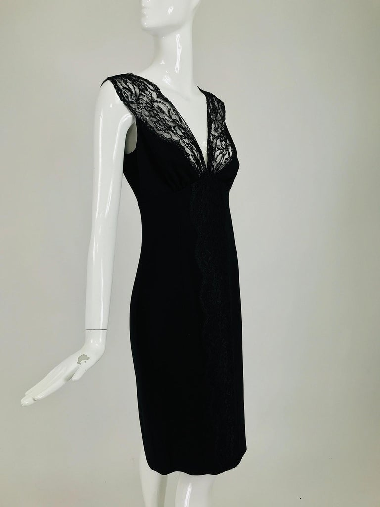 Valentino sleeveless black sheath with black lace décolletage. Plunge V bodice with unlined black lace facings, empire waist, the skirt is semi fitted. Back center hem vent. Black flat wool with some stretch. Fully lined in black acetate. Closes at