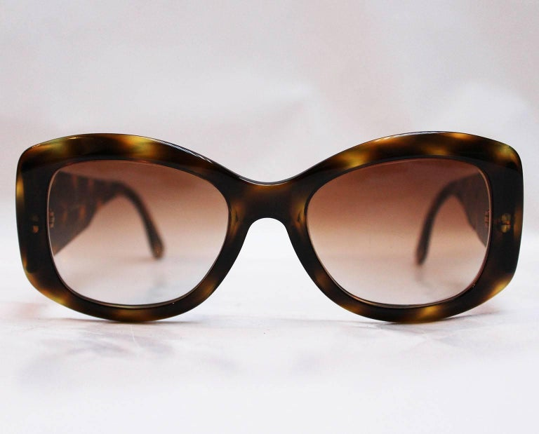 A great pair of sunglasses by Italian fashion house Valentino. In wonderful shades of brown, with wide arms these glasses are a chic addition to any wardrobe. On the inside of the right arm is stamped, Valentino , made in Italy, and on the inside of