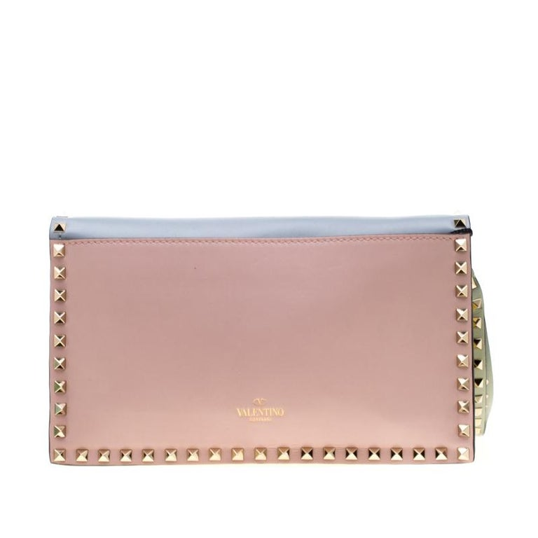 This Valentino leather wristlet clutch is a statement piece to add to your closet. Designed with different colours of leather and lined with Rockstuds on the hand slot and wristlet, this clutch is high on style. The interior is lined with leather