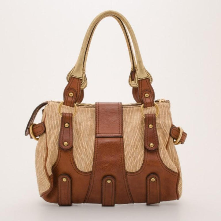 Go for a wearable yet adventurous look with this V woven leather satchel from Valentino. Crafted from woven leather with smooth brown leather trim, the exterior is detailed with a large jeweled gold Valentino logo, gold hardware, rolled gold leather