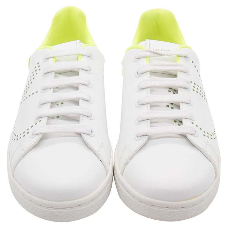 Make effortless style statements in these white and fluorescent green sneakers from Valentino! They are crafted from leather and feature round toes and lace-ups on the vamps. They have been styled with perforated V-logo details on the sides and the