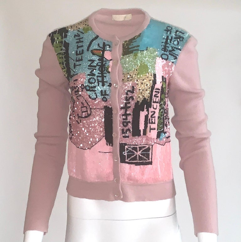 Amazing and rare mauve pink rib-knit wool-cashmere cardigan from the 2006 Valentino collection created with Basquiat prints. Front sweater is covered in pink, black, robin's egg and lime sequins creating an iconic Basquiat work. Long sleeve, button