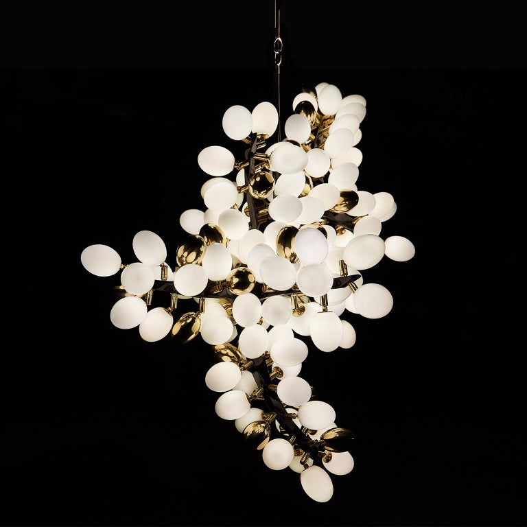 Inspired by the resplendent natural forms of ancient flora, this collection is rigorously crafted in hand-blown Murano glass and solid sculpted bronze (or stainless steel).  Description: Vertical Valiant Chandelier  Dimensions: Approx. 36