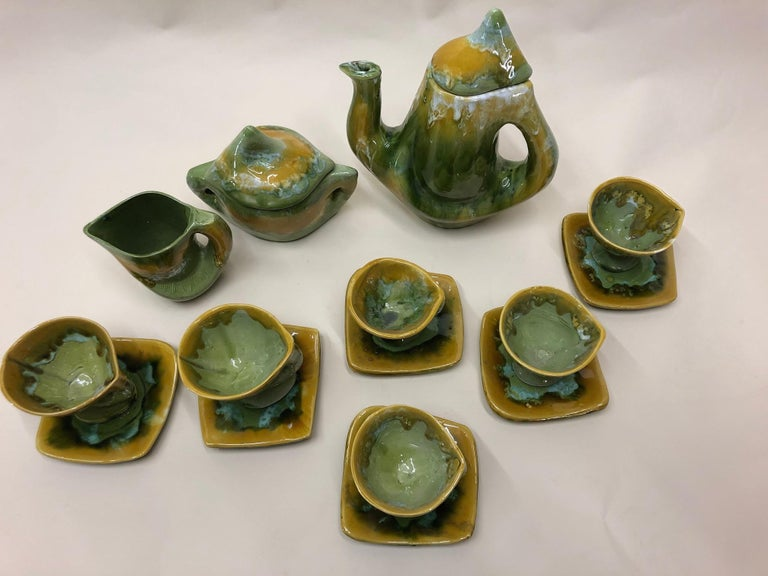 Fabulous design of a luscious green and oker yellow Vallauris ceramic coffee set. This contemporary and complete set has a coffee pot, sugarbowl, creamer and six cups and saucers. The set has been made in the 1960s. The 9 piece set is a rich hand