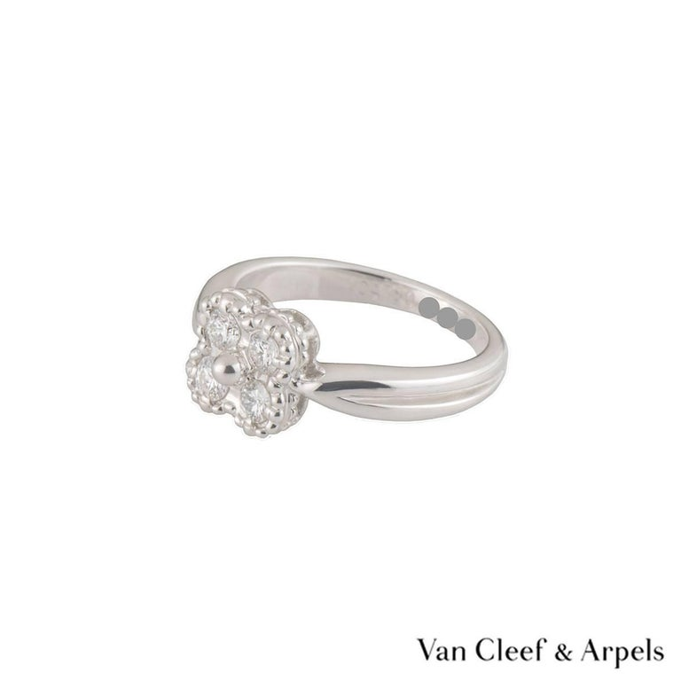A lovely 18k white gold Van Cleef & Arpels diamond ring from the Alhambra collection. The central flower motif is set with 4 round round brilliant cut diamonds in a pave setting weighing approximately 0.28ct, G colour and VS clarity. The ring is