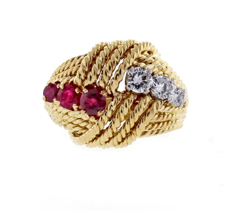 From Van Cleef & Arpels a 1960s cocktail ring with rubies and diamonds. The  18 karat gold ring features three brilliant diamonds weighing approximately .40 carats and three red rubies withing approximately .50 carats. Signed and numbered, made in