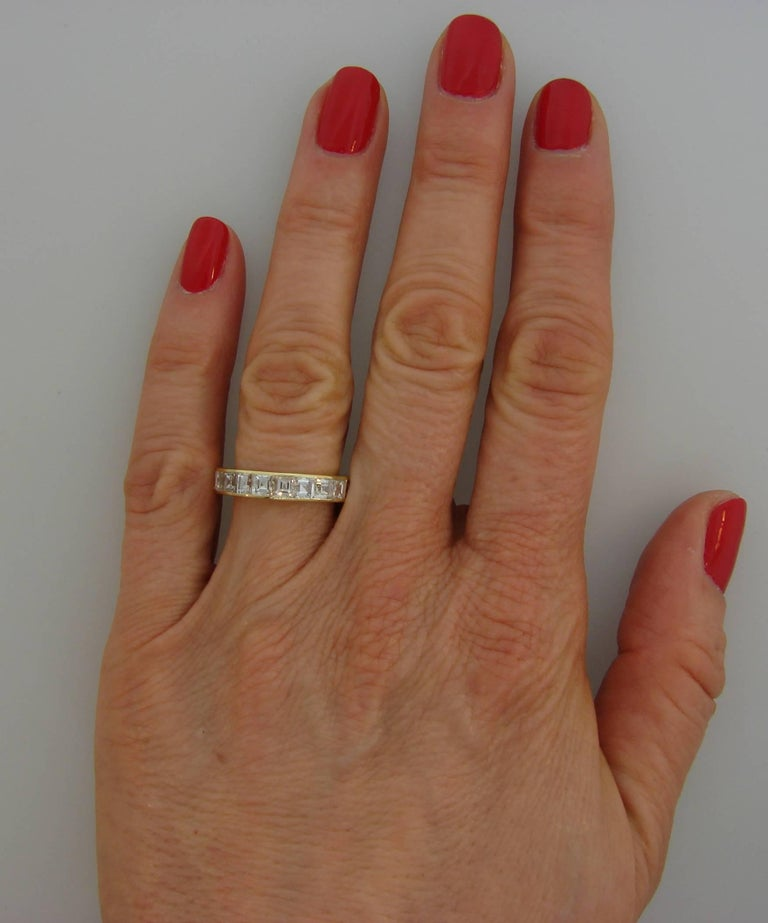Classy and timeless eternity band created by Van Cleef & Arpels.  It is made of 18 karat yellow gold and twenty one asscher cut diamonds (F color, VVS clarity, total weight approximately 4.20 carats).  The band is size 6.75-7. It is 4.2 mm wide and