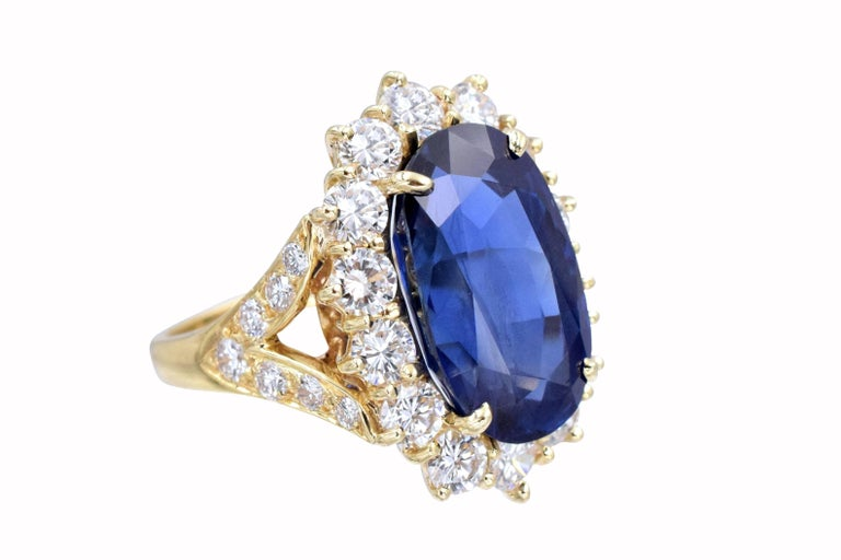 Van Cleef and Arpels Burmese sapphire and diamond ring.  Set with natural no enhancement oval old cut Burmese 12.01 carat sapphire, surrounded by 14 fine quality  brilliant shape diamonds. Sides are V shaped leaves with 7 encrusted diamonds each