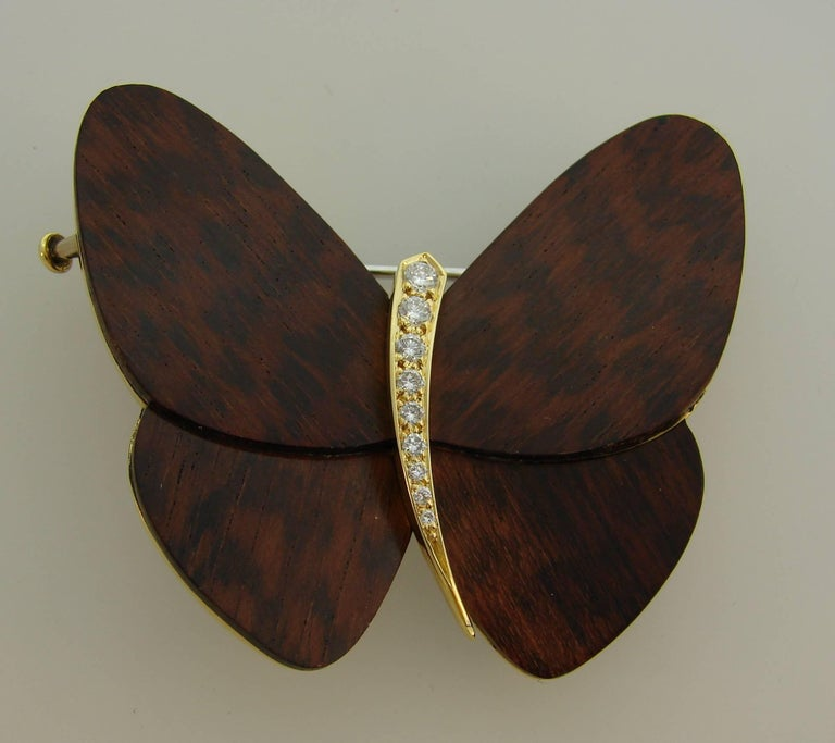 Signature Van Cleef & Arpels butterfly clip. Gracious and feminine, the brooch is a great addition to your jewelry collection. Beautiful lines, perfect proportions - the highlights of this lovely brooch.  Made of wood and 18 karat yellow gold and