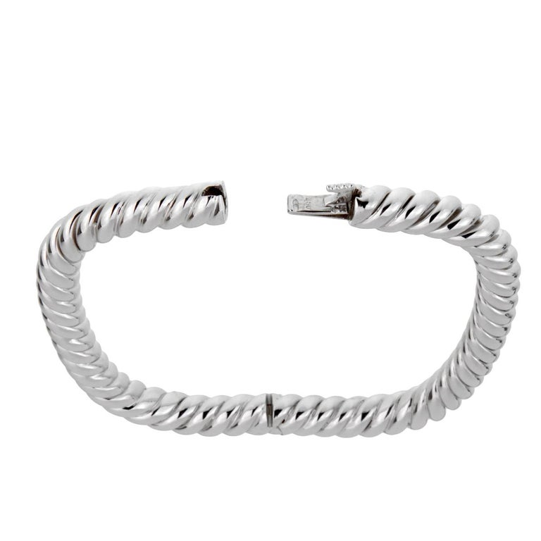 A fabulous Van Cleef & Arpels bangle bracelet circa 1990's featuring a braided design in glimmering 18k white gold. The bracelet was just cleaned and serviced and is accompanied with the documents from Van Cleef & Arpels.  Wrist Size: Upto 7 1/2