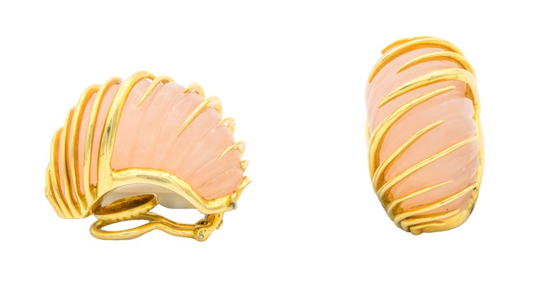A pair of Van Cleef and Arpels earrings each featuring a carved rose quartz crystal encased by staggered tapered knife edge bands - in 18K yellow gold
