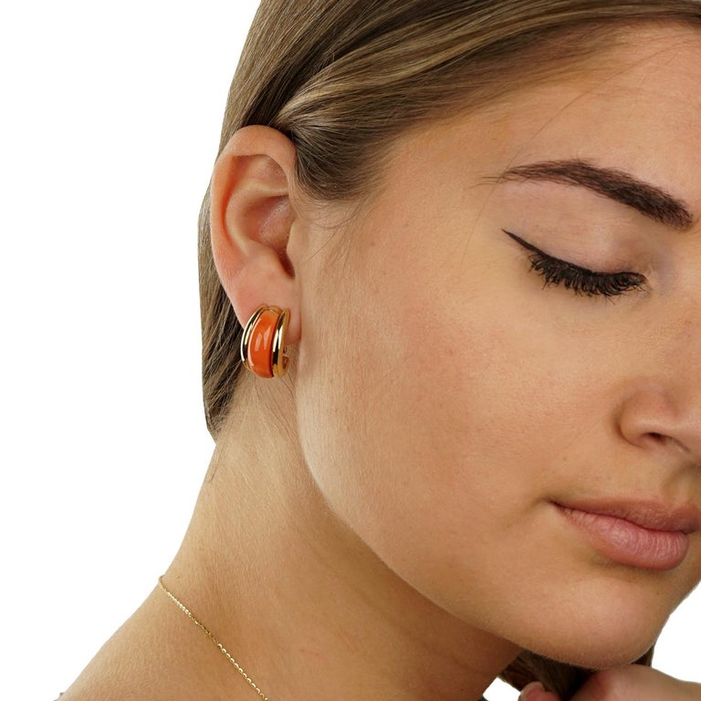 A fabulous pair of authentic Van Cleef & Arpels earrings featuring a carved coral which acts as a centerpiece delicately placed in 18k yellow gold.  Length: .78