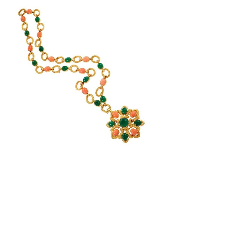 A French gem-set sautoir by Van Cleef and Arpels. The necklace is a textured 18 karat gold link chain with collet-set oval coral cabochons alternating with chrysoprase cabochons.  A detachable pendant/brooch of rosette