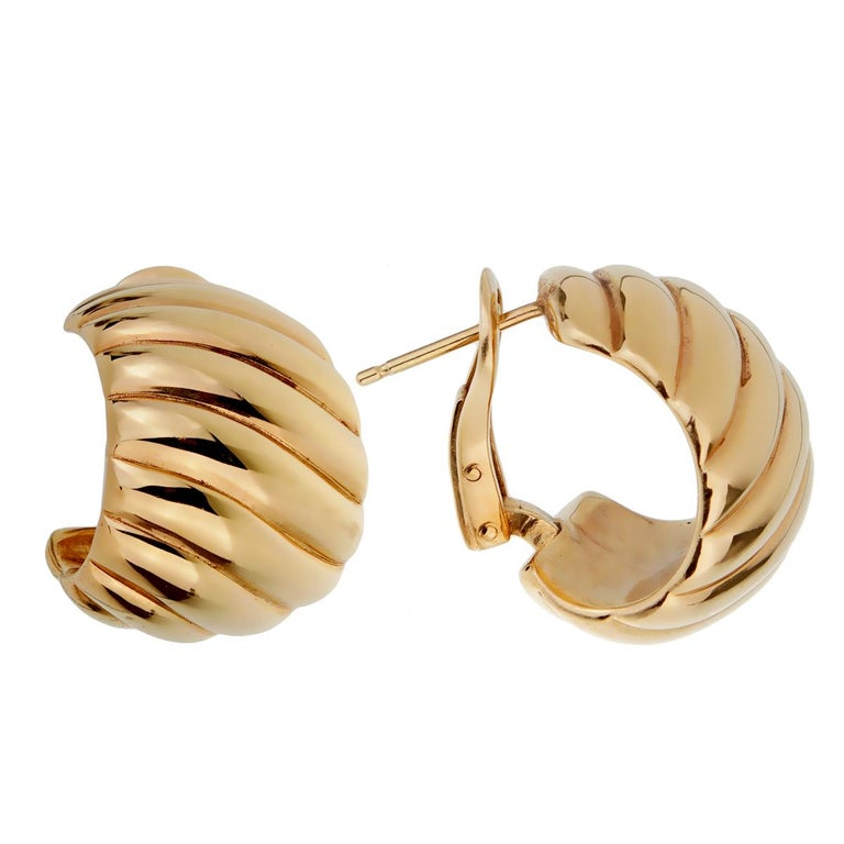 A fabulous pair of vintage Van Cleef and Arpels earrings featuring a waved design in polished 18k yellow gold. These classic gold earrings are perfect for everyday wear.  The earrings measures .82