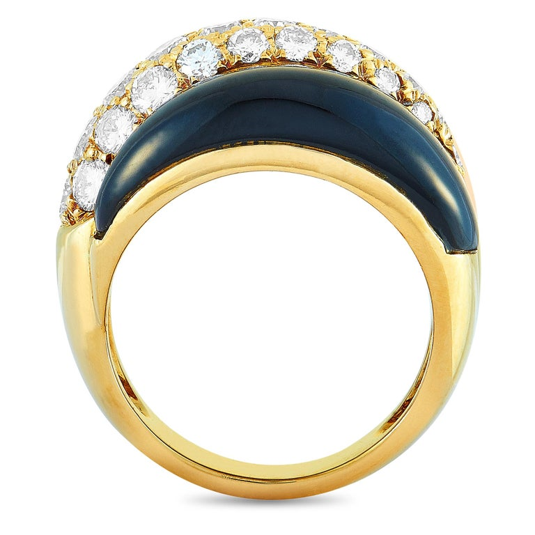 This Van Cleef & Arpels ring is made of 18K yellow gold and decorated with black and pink coral and a total of 1.42 carats of diamonds. The ring weighs 10.5 grams, boasting band thickness of 4 mm and top height of 7 mm, while top dimensions measure