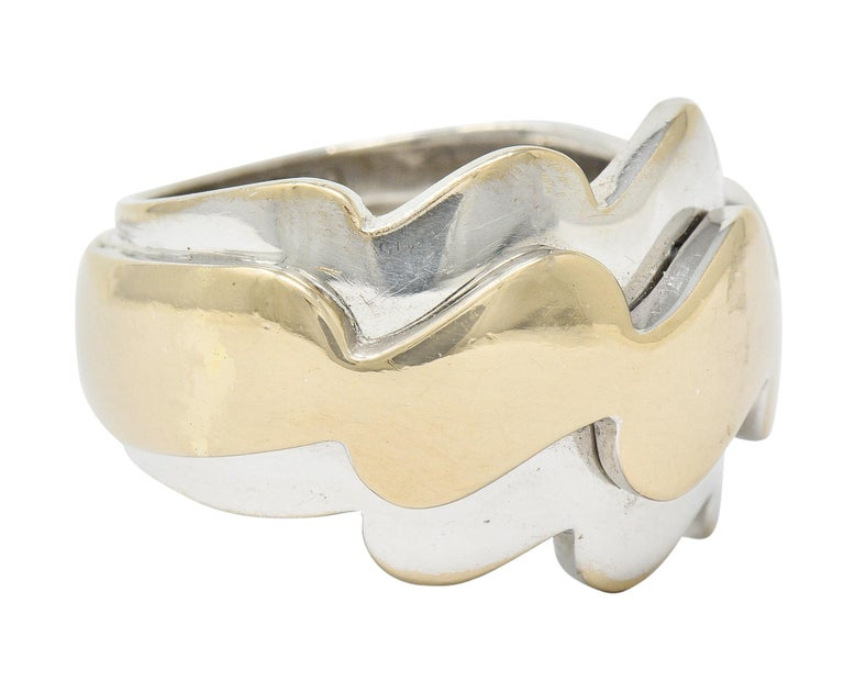 Two-tone gold band ring is designed as three waved segments  Central wave is raised and a muted yellow gold color that is flanked North and South by white gold waves  Numbered and signed VCA with maker's mark  Stamped 750 and with French assay mark
