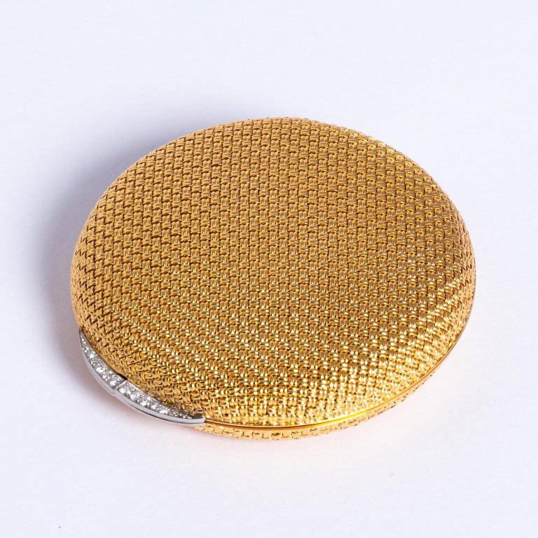 Stunning 1950s 18-karat yellow gold and diamond compact, round shape, with a woven design and a crescent diamond set thumb-piece. Stamped 18K in a shield like mark on the inner ring of the compact, Signed Van Cleef ET Arpels, made in France with a