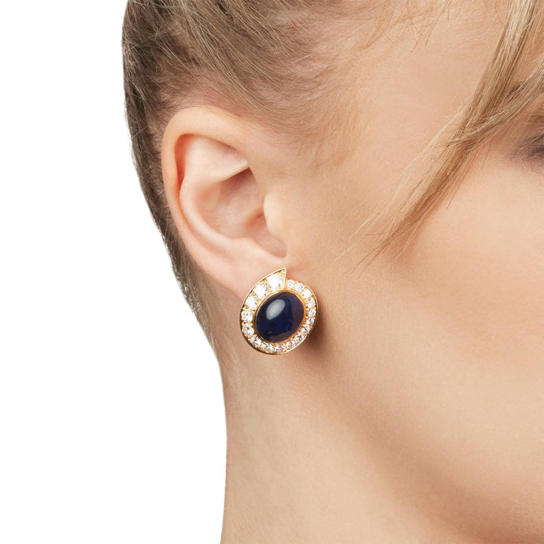 These Earrings by Van Cleef & Arpels feature two cabochon Sapphires of 34.00ct total surrounded by 34 round brilliant cut Diamonds of 5.00ct total colour E-F, clarity VVS, made in 18k Yellow Gold. These earrings have clip-on backs. Complete with