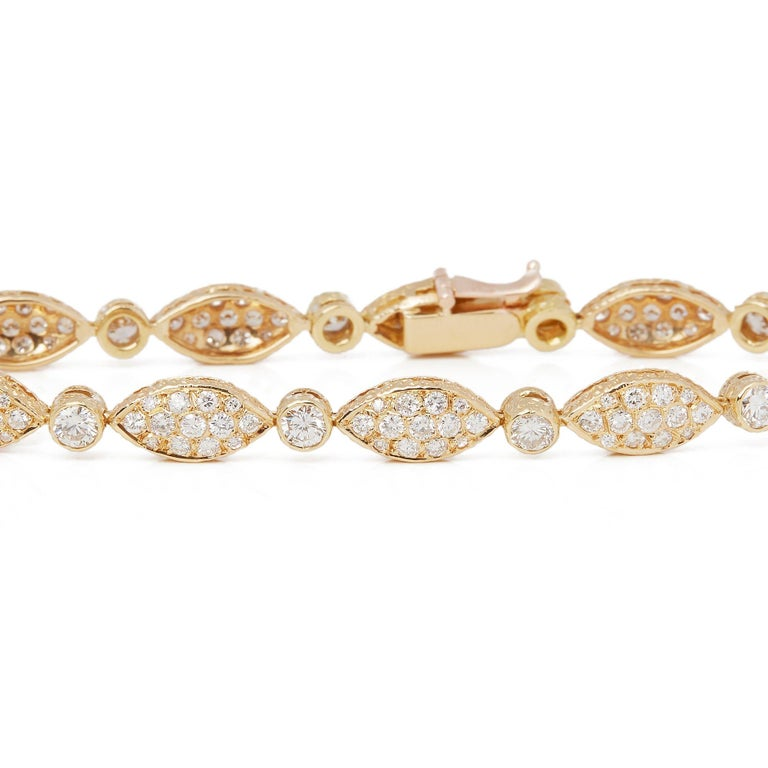 This Vintage Bracelet by Van Cleef and Arpels features Eleven Sections Set with Pave Round Brilliant Cut Diamonds Totalling 4.51cts with indvidual Rub Over Set Round Brilliant Cut Diamonds set in between Totalling 1.10cts. With Tongue Clasp and