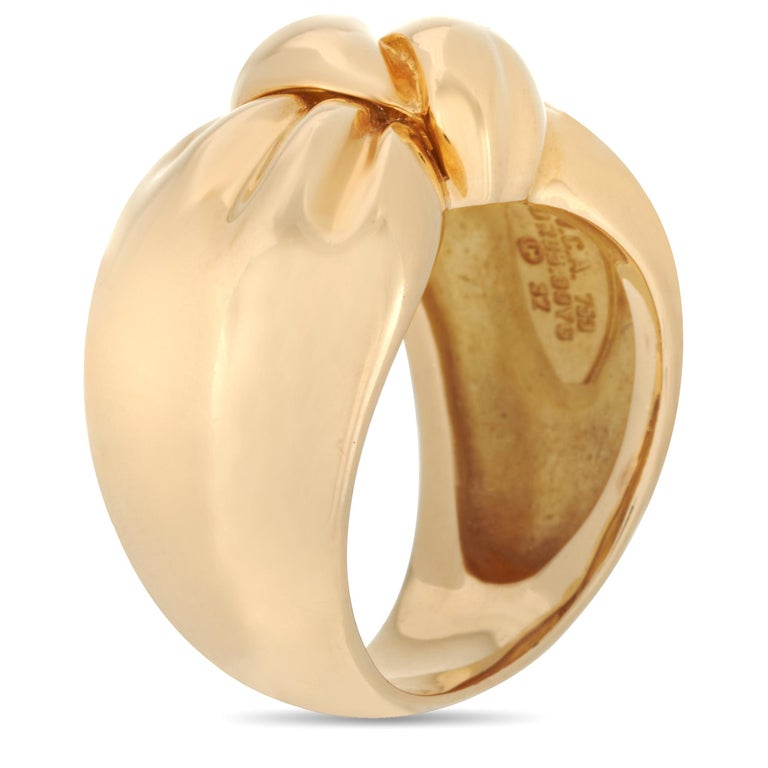 This Van Cleef & Arpels turban ring is crafted from 18K yellow gold and weighs 13.2 grams. It boasts band thickness of 8 mm and top height of 6 mm, while top dimensions measure 10 by 20 mm.    The ring is offered in estate condition and includes the