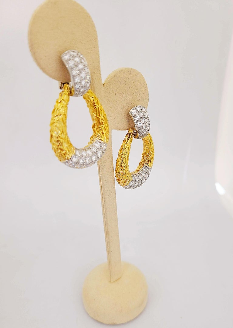 Crafted out of 18K yellow gold, composed of an articulated hoop, in a classic  Chevalerie door knocker motif circa 1970, set with round-cut diamonds, weighing a total of approximately 5.55 carats, backs are clip-on; each earring measures 1-7/8 x