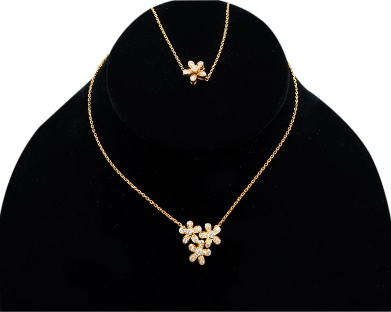 A beautiful necklace from the Van Cleef & Arpels Socrate Collection.  Featuring 3-Flower pendant embellished with 0.91 carats of diamonds. Made in 18K yellow gold.