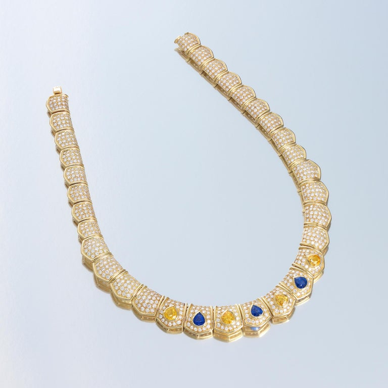 Van Cleef & Arpels dazzling collar necklace bursting with brilliance of approximately 19 carats of finest white diamonds which are complemented by 11 carats of vividly-colored blue and yellow sapphires, all masterfully set in 18 karat yellow gold.