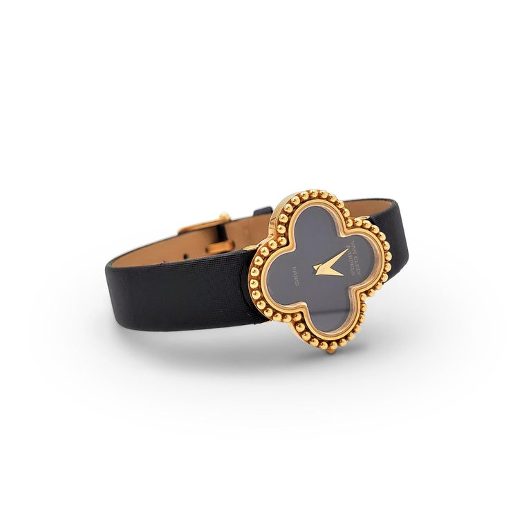 Authentic Van Cleef & Arpels 'Alhambra' watch. Centering on the classic clover motif, the watch bezel and case (26mm x 26mm) are crafted in 18 karat yellow gold. A chic black onyx dial features gold-toned sword-shaped hands and signed Van Cleef &