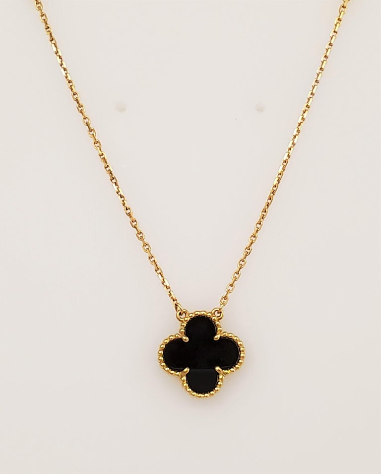 Authentic Van Cleef & Arpels Alhambra motif necklace crafted in 18 karat yellow gold featuring an onyx clover-shaped pendant.  Signed VCA, Au 750, with serial number and hallmarks.  Chain measures 16 inches in total length and can be worn at a 7 or