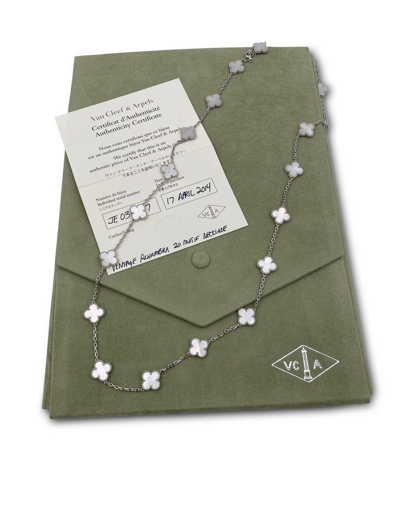 Authentic Van Cleef & Arpels 18 karat white gold long necklace featuring 20 clover leaf inspired motifs set with carved mother-of-pearl stones. The necklace is presented with original Van Cleef & Arpels box and papers. Measures 32 1/2 inches in