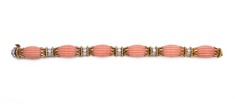 Van Cleef & Arpels Angel Coral & Diamond Bracelet  Composed of fluted carved coral links, spaced by gold motifs, highlighted with round diamonds. Diamonds, estimated to weigh a total of approximately 1.60 carats.  Internal circumference is 61⁄4