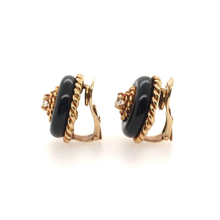 A pair of 18 karat yellow gold, black onyx and diamond earrings. Van Cleef and Arpels. Circa 1960. Of dome design, set with black onyx, enhanced by gold ropework, centering a circular cut diamond, each weighing approximately 0.20 carats. Diameter is