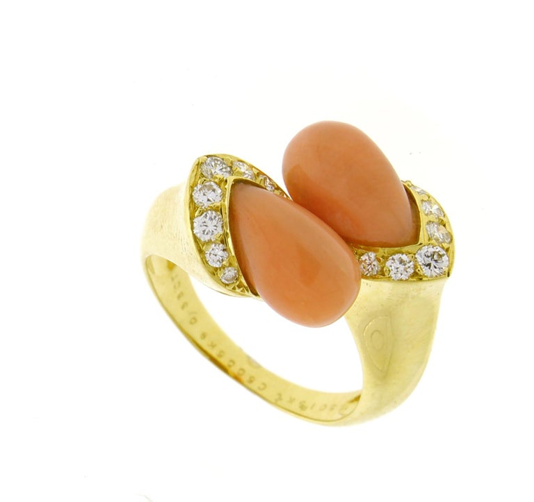 From Van Cleef & Arpels  an orangey-pink coral and diamond bypass ring. ♦ Designer: Van Cleef & Arpels ♦ Metal: 18 karat ♦ 16 Diamonds = .32 ♦ Coral 11 X 6mm ♦ Circa 1970s ♦ Size 6½, Resizable ♦ Packaging: presentation box  ♦ Condition: Excellent ,