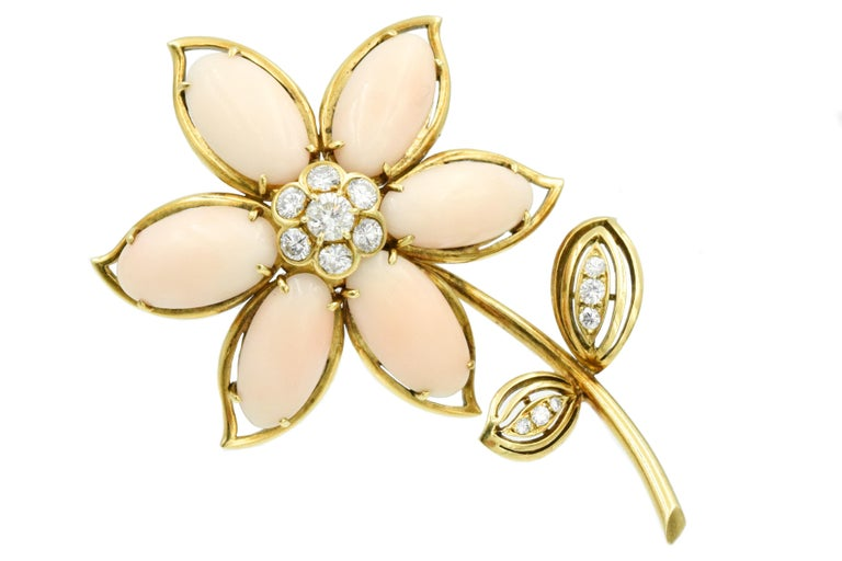 Floral design, the petals composed of 6 coral cabochons,accented by round diamonds. Estimated weight of the diamonds is 1.70carats Signed Van Cleef & Arpels N.Y. Serial # xxxxxx
