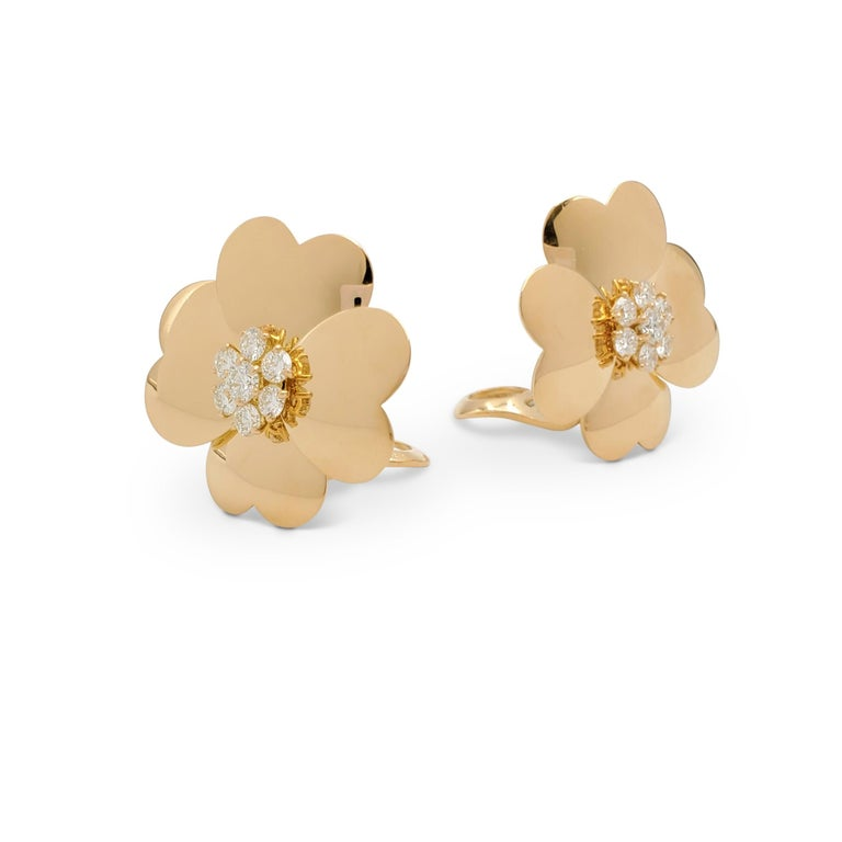 Authentic Van Cleef & Arpels earrings from the iconic 'Cosmos' collection. Designed as a pair of flowers composed of four heart-shaped petals crafted in 18 karat yellow gold. The centers are highlighted with round brilliant cut diamonds (E-F color,
