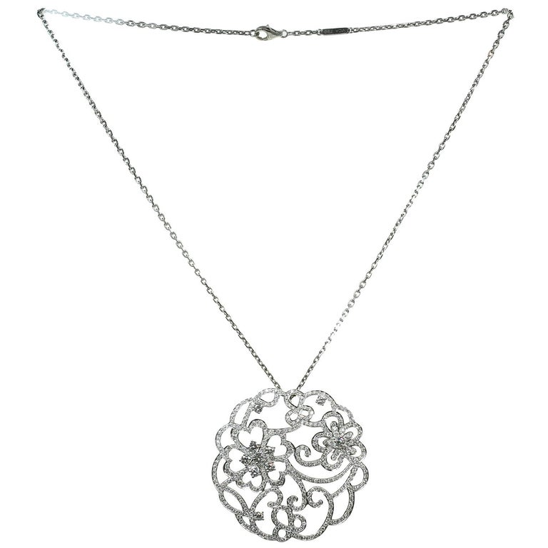 This exquisite Van Cleef & Arpels Dentelle collection necklace is crafted in 18k white gold and features a round open-work pendant set with brilliant-cut round D-F VVS1-VVS2 diamonds. Made in France circa 2000s. Measurements: 2.04