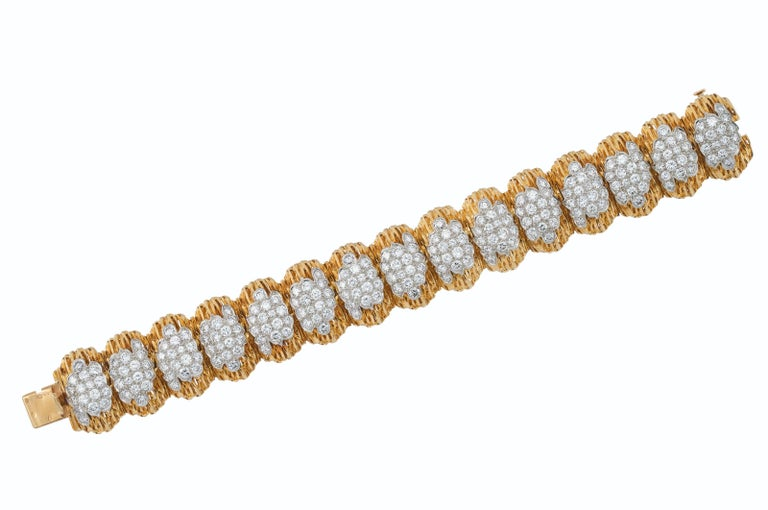 This Van Cleef & Arpels bracelet features 240 Round diamonds weighing approximately 9-10 carats, F-G color, VVS-VS. The textured 18k yellow gold and platinum with French marks is in very good overall condition showing normal signs of wear. Circa