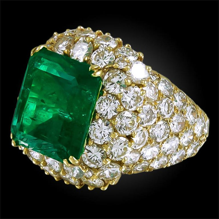 A divine ring, exceptionally crafted by Van Cleef & Arpels, centering a 12 carat emerald cut emerald of brilliant color, surrounded by brilliant round cut diamonds mounted in 18k yellow gold.