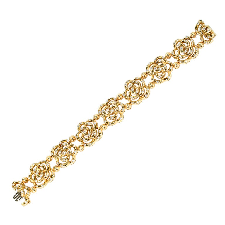 An elegant and chic Van Cleef & Arpels 18kt high-polish yellow gold openwork blossom bracelet with eight camellia motifs sprinkled with 120 round brilliant-cut diamonds weighing approximately three carats of E/F color and VVS/VS clarity. The