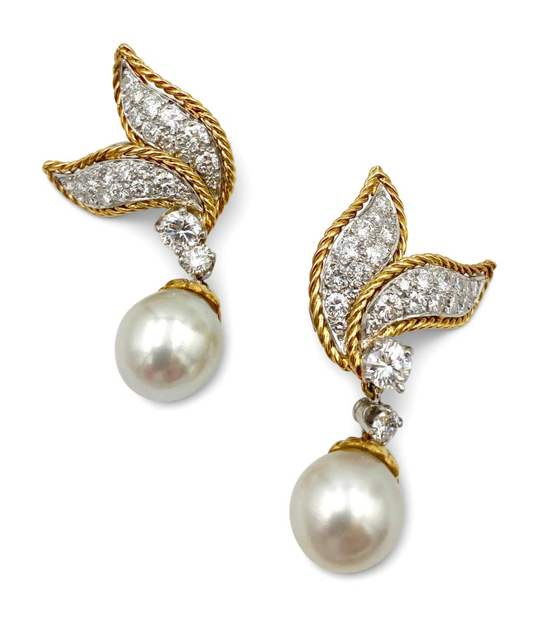 Vintage 1960s Van Cleef & Arpels diamond and pearl ear clips made in 18 karat yellow gold. The earrings feature a leaf motif set with round brilliant cut diamonds (E-G in color, VS clarity) of an estimated 2.0 carats set in platinum and completed