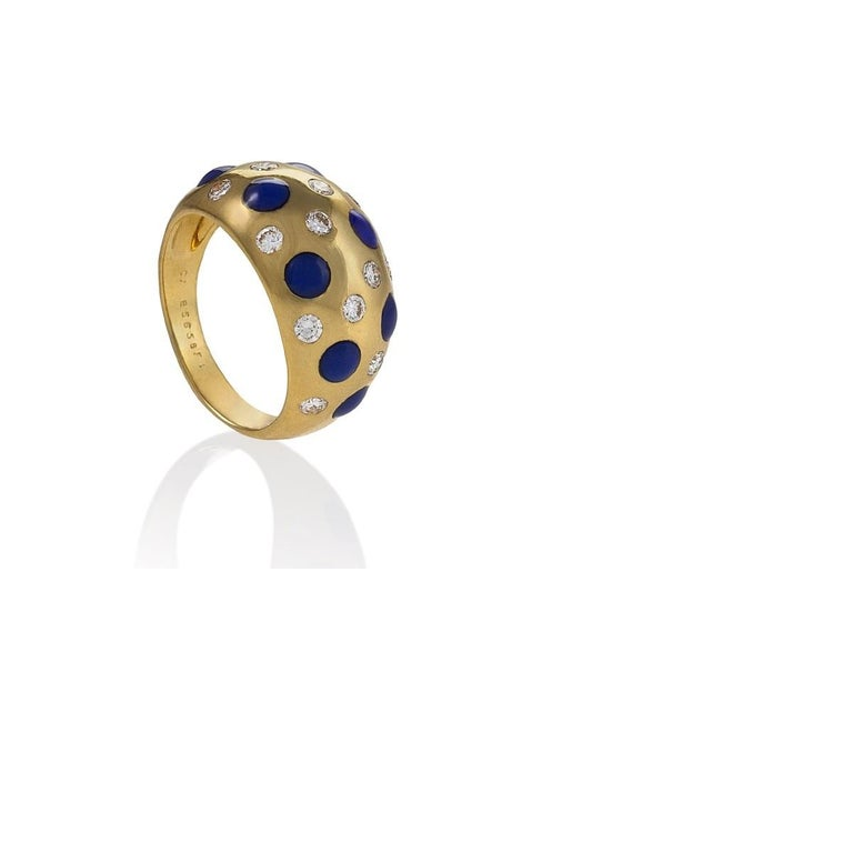 A French 18 karat gold ring with diamonds and sapphires by Van Cleef & Arpels. The is ring has 13 round brilliant cut diamonds with an approximate total weight of .65 carats, and 8 cabochon sapphires with an approximate total weight of .96 carats.