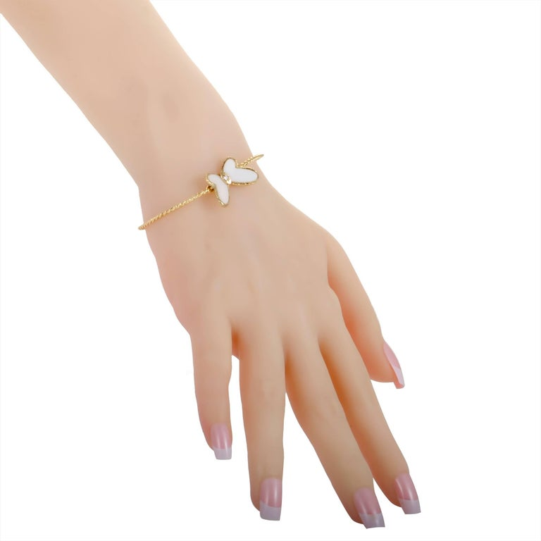This stunning bracelet by Van Cleef & Arpels is bound to embellish any arm it is worn on! Beautifully designed in 18K yellow gold, the delicate bracelet has a butterfly accented with white coral wings and one sparkling diamond that enhances the