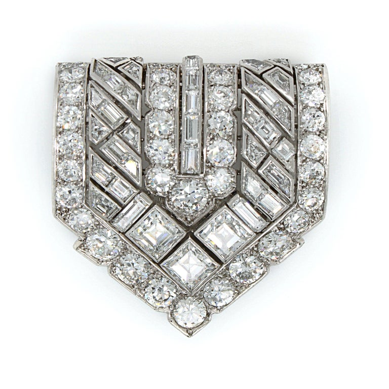 A collective Van Cleef & Arpels diamond Art Deco clip, French, ca. 1920s.   The clip is set with round brilliant cut and rectangular cut diamonds in a geometric manner, making the clip very wearable for any occasion. The diamonds are of very fine