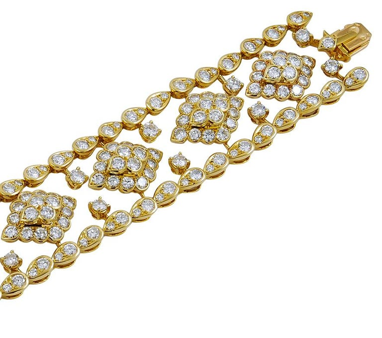 A resplendent statement piece, beautifully executed 18k yellow gold bracelet set with two rows of brilliant-cut diamonds mounted in drop shaped yellow gold, connected by several brilliant-cut diamonds that combine to form floral motifs in the