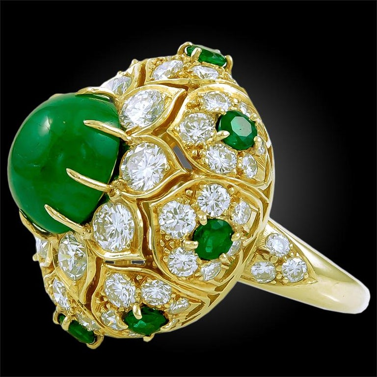Exceptionally crafted by Van Cleef & Arpels, comprising an 18k yellow gold ring, embellished with  brilliant round cut diamonds and round cut emeralds, centering a large cabochon emerald of magnificent color. Signed Van Cleef & Arpels. ring size –