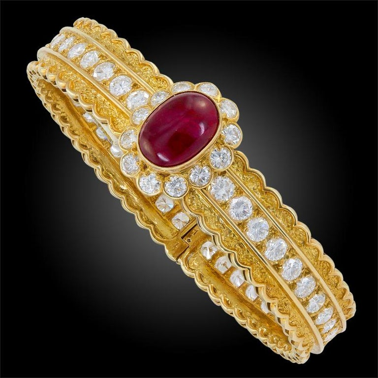 An 18k yellow gold bangle bracelet, set with brilliant-cut diamonds and cabochon ruby, signed Van Cleef & Arpels. Inner circumference is approx. 160mm Made in France